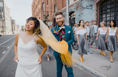 Bride and groom walking just off the curb in the street, smiling bride in the front holding up her dress while groom in teal suit holds her yellow ombre veil and the wedding party walks on the sidewalk in Greenpoint Brooklyn