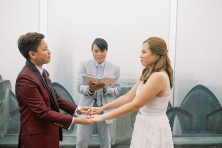 Butch/femme Asian couple holding hands and looking at each other with smirky smiles listening to the intro of their ceremony officiated by lgbtq+ officiant from Once Upon A Vow at Top of the Rock.
