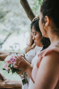 Profile photo of bridesmaid and sister of the groom looking down at a piece of paper, reading a quote during the Spanish elopement ceremony officiated by bilingual wedding officiant from Once Upon A Vow in Cop Cot, Central Park