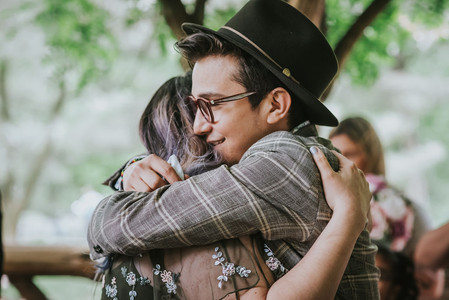 Photo of a smiling guest wearing a plaid blazer and hat hugging the bride post-ceremony led by Spanish wedding officiant from Once Upon A Vow in Central Park's Cop Cot