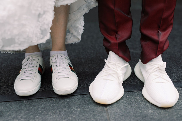 Picture of both brides' comfortable white sneakers on Times Square NYC asphalt; picture taken post ceremony officiated by queer officiant at Once Upon A Vow.
