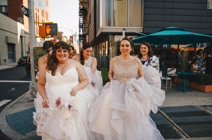 Close up shot of two brides about to cross a Downtown NYC crosswalk with their three three friends helping them keep the backs of their dresses from dragging on the floor; all are smiling as they make their way to HousingWorks in Manhattan for their ceremony, which is officiated by Once Upon A Vow.