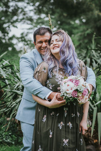 Candid photo of groom in blue suit embracing his new purple-haired wife from behind as she smiles with eyes closed and holding the bouquet set among Central Park's greenery