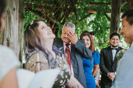 Candid photo overlooking the right shoulder of Spanish-speaking wedding officiant from Once Upon A Vow as the bride looks skyward laughing, groom smiling, and in focus the father of the bride wipes a tear and guests smile in the background at Central Park's Cop Cot