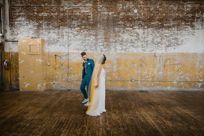 First look candid photo in Greenpoint Loft of bride and groom where groom walks around bride checking out her gorgeousness and the cool ombre yellow veil
