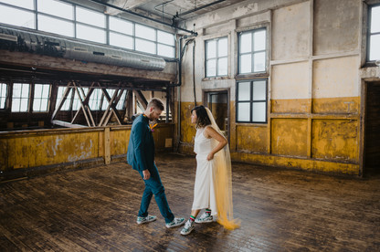 First look at the Greenpoint Loft where bride and groom are standing across from each other showing off their tropical converse shoes