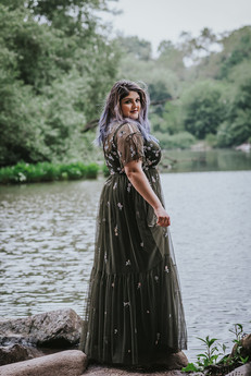 Portrait of purple-haired bride wearing an olive green sequined dress facing towards the right while looking at the camera, the background is of the pond and greenery in Central Park