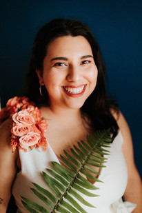 Smiling bride portrait looking at the camera wearing a pink floral shoulder piece and holding a tropical looking leaf across her chest.