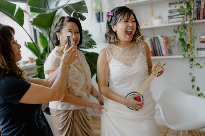 Candid photo of joyful, laughing bride playing with a watermelon ukele while her mom stands behind her, holding her dress, and a woman dressed in black takes a photo set among white curated background with plants all around