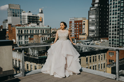 Picture of caucasian bride in champagne dress leaning against the railing of the rooftop with Downtown Manhattan buildings in the background; picture taken before ceremony officiated by lgbtq+ officiant at Once Upon A Vow..