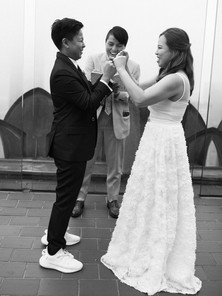 Black and white picture showing butch/femme Asian couple fist pounding each other mid ceremony following a line from the ceremony officiated by queer officiant from Once Upon A Vow at Top of the Rock.