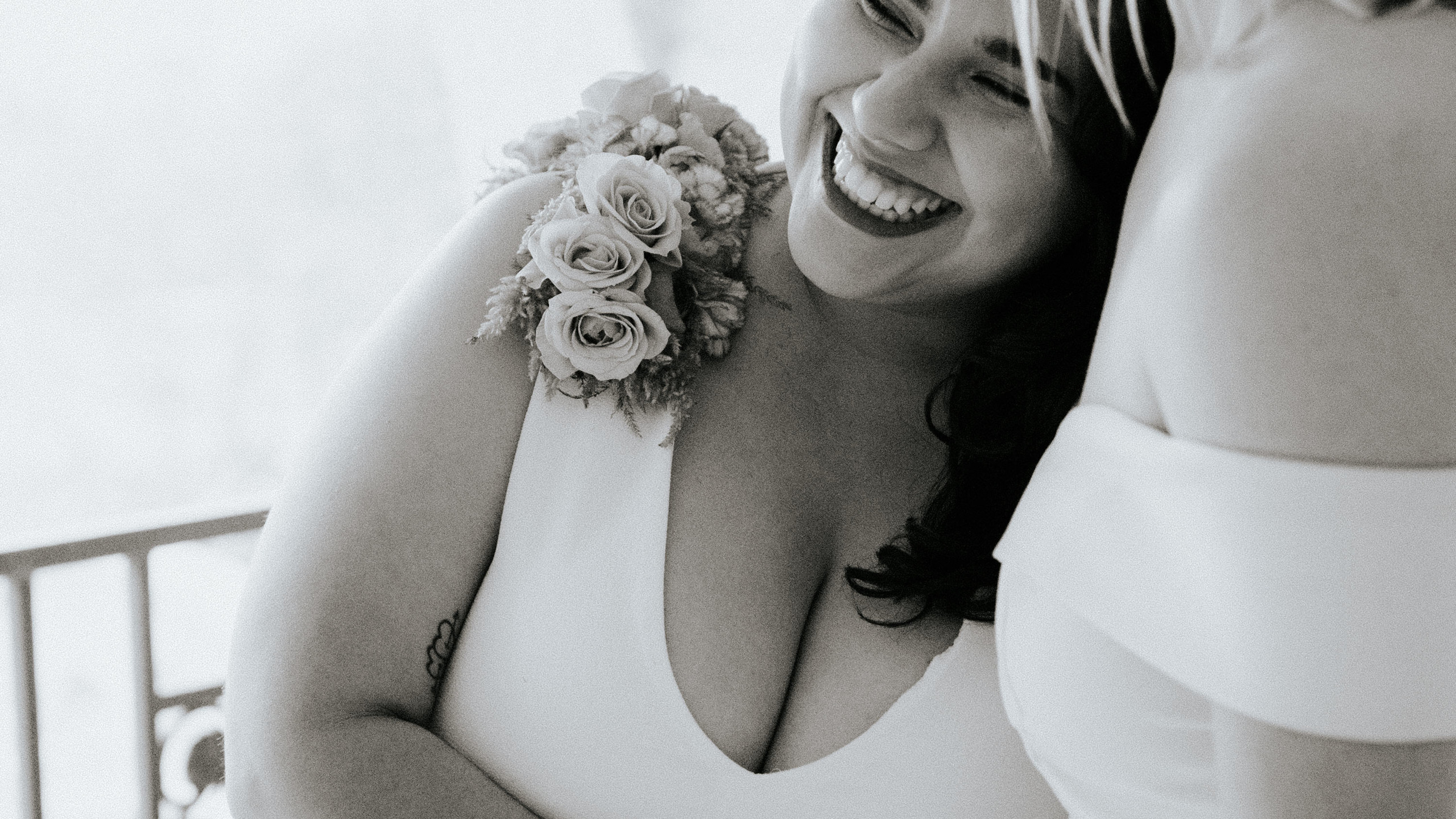 Black and white close-up photo of smiling Latina bride with floral shoulder piece resting her head on her partner's chest