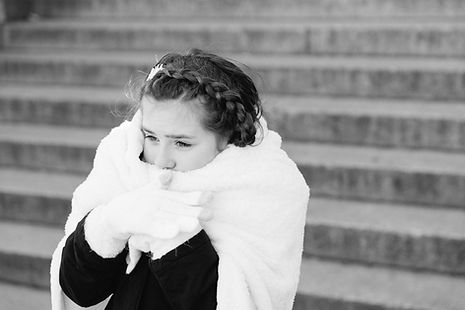 Black and white photo of little girl wearing a white scarf and gloves covering her mouth for an outdoor Central Park winter elopement
