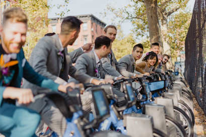Fun NYC photo of the couple and groomsmen on Citi bikes; groom all the way to the left slightly out of focus with four groomsmen in grey suits to his left, the bride competitively smiling and two more groomsmen to her left in Greenpoint, Brooklyn