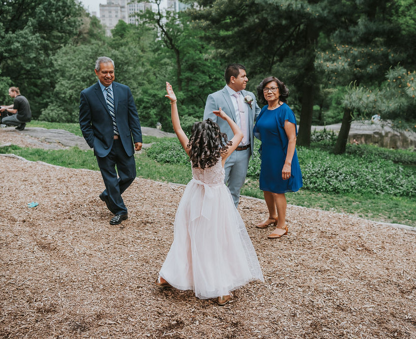 Candid photo focused on dancing flower girl while the groom and his parents are standing around right outside of Central Park's Cop Cot right before the bilingual elopement ceremony officiated by Spanish-speaking officiant from Once Upon A Vow