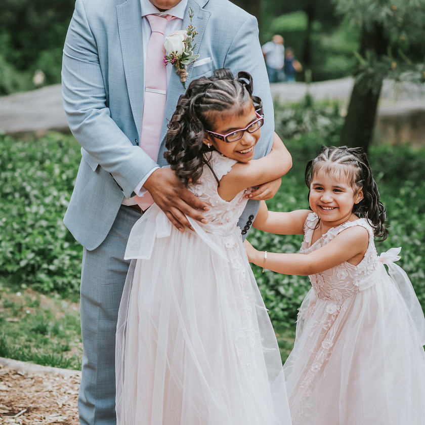 Candid photo of two giggling flower girls dressing in light blush pink as they embrace the groom in Central Park's Cop Cot before the elopement officiated by bilingual wedding officiant from Once Upon A Vow begins