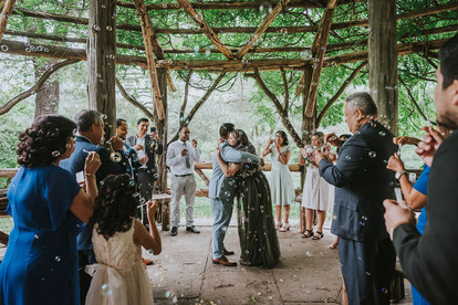 Wide photo of guests blowing bubbles in celebration with the couples in the center hugging after their Spanish elopement ceremony held in Central Park's Cop Cot