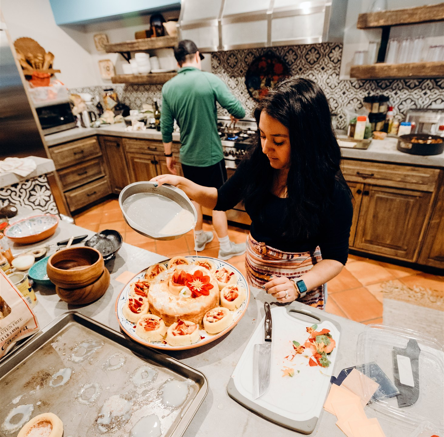 Mary-Beth from Heart of Celebration pouring delicious creamy goodness onto dessert with floral flowers that she has created, while in the kitchen working alongside her husband