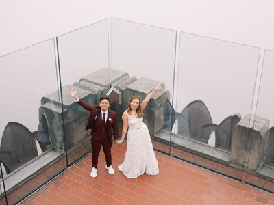 At Top of the Rock, butch/femme Asian couple waving with one hand while holding hands and smiling; shot is from above and taken post ceremony officiated by queer officiant at Once Upon A Vow.