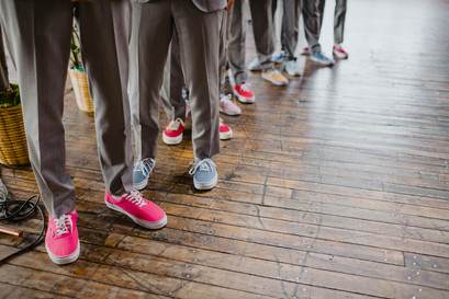Photo of groomsmen's colorful ked sneakers while they're standing and waiting for the couple to walk down the aisle during the ceremony officiated by Once Upon A Vow in Greenpoint Loft