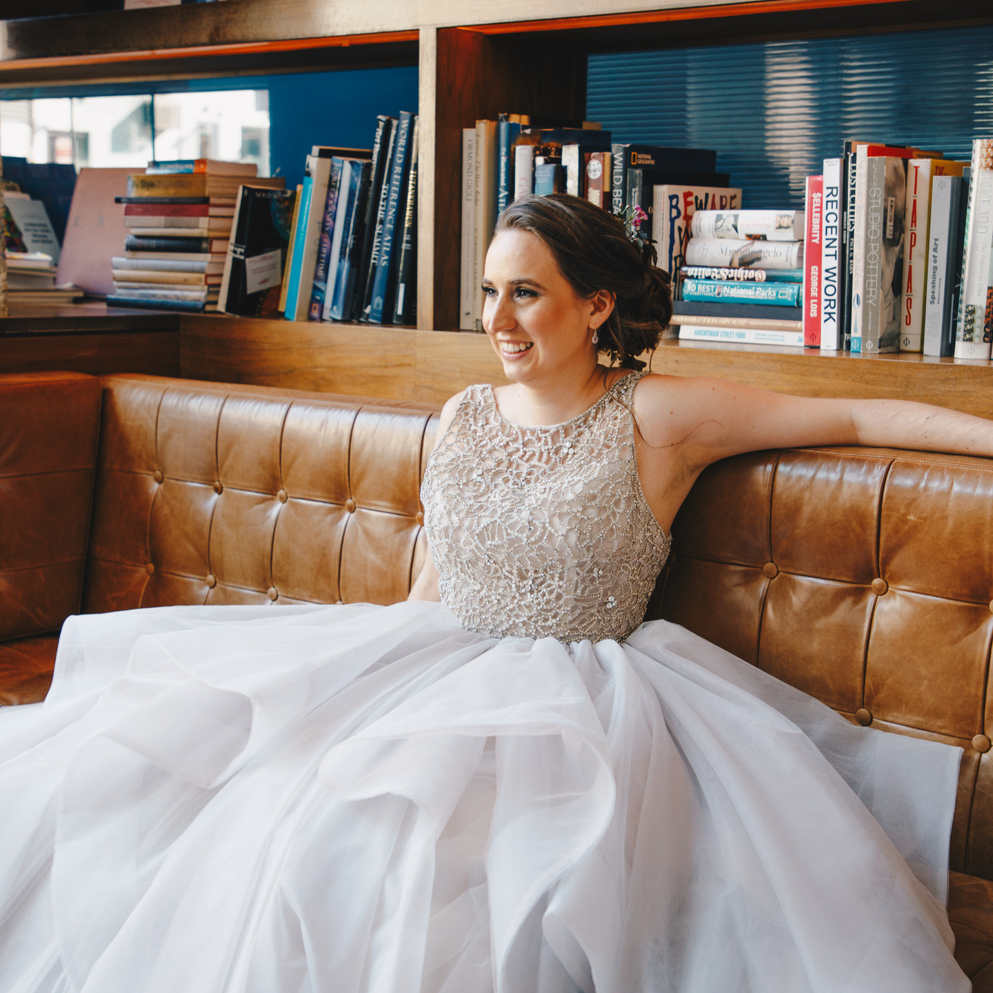 This wide shot of caucasian bride sitting confidently and openly with left arm across back of gorgeous brown couch; behind her are lots of books and she's looking in the opposite direction of those books toward her future; she's smiling and excited about getting married queer officiant at Once Upon A Vow at HousingWorks.