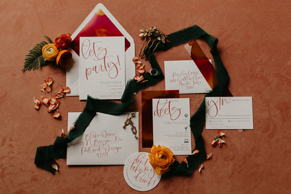 Flat lay photo of invitation suite that shows the envelope, the RSVP card, the location and logistics card with a vintage hair clip, bright orange florals, and olive green ribbon spiraled throughout