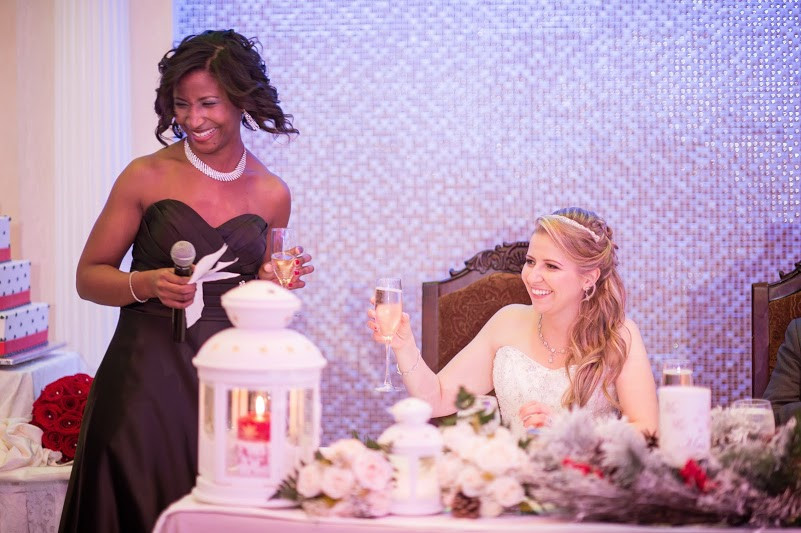 Maid of Honor laughing while giving her Maid of Honor speech while holding the champagne glass and to her left, the bride is smiling and holding her champagne glass as well