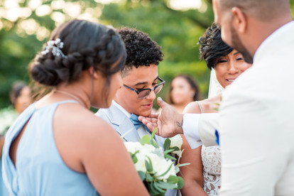 During the ring warming ritual in the bilingual ceremony, the groom wipes away son's tears and the bride and mother cries during the bilingual wedding ceremony officiated by Once Upon A Vow at Pelham Bay Golf Course