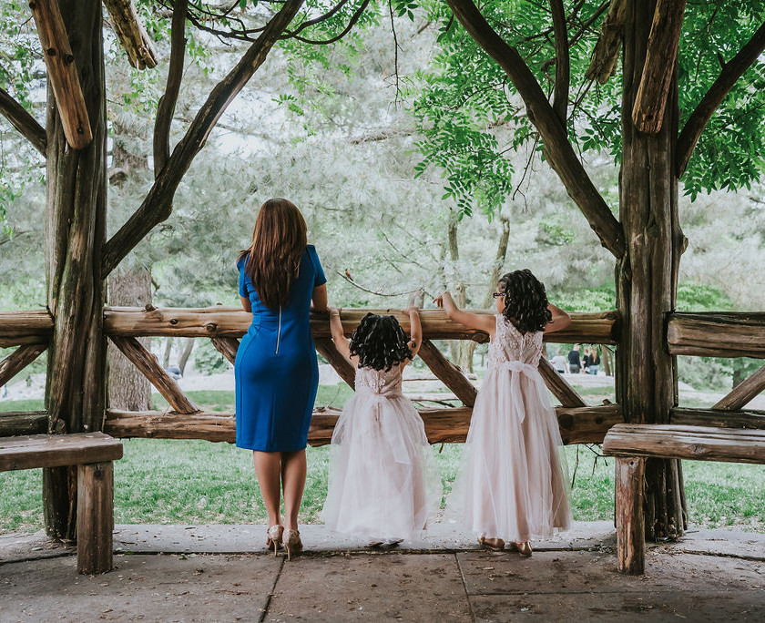Sweet photo of mother of the bride dressed in royal blue and two flower girls looking out over the greenery in Central Park's Cop Cot right before the elopement ceremony officiated by Spanish-speaking officiant from Once Upon A Vow