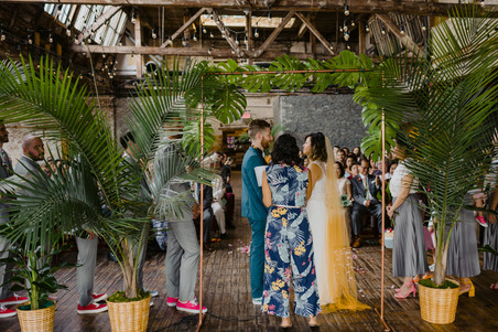 Photo of the ceremony officiated by Once Upon A Vow taken from behind the officiant dressed in a tropical jumpsuit with botanical ceremony set up, where the couple is staring into each other's eyes in Brooklyn's Greenpoint Loft.