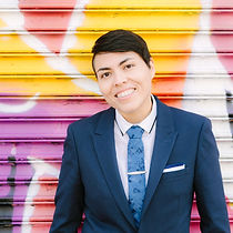 smiling, bilingual spanish and english speaking wedding officiant in blue suit and tie with colorful mural background in Brooklyn, NY