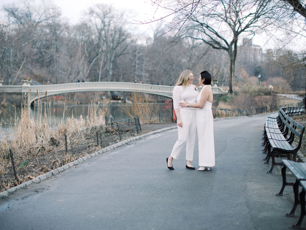 Post elopement ceremony officiated by lesbian officiant at Once Upon A Vow, two brides looking at each other lovingly, one in a white halter-top jumpsuit and the other in nice white pants and a sweater blouse; they're on a path towards Bow Bridge, which you see in this Central Park backdrop.