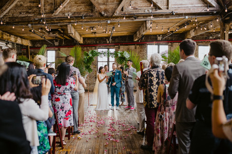 All guests are standing during the group sing-a-long while the focus is on the couple singing their personalized song together led by fun NYC officiant from Once Upon A Vow in Brooklyn's Greenpoint Loft
