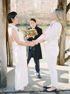 Asian-Canadian and Anglo-American brides holding hands and looking at each other lovingly, one in a halter-top jumpsuit and the other in nice pants and a sweater blouse; standing before their queer officiant from Once Upon A Vow, a masculine of center woman in a dark grey outfit and black coat holding the ceremony book which has a flowery green cover.