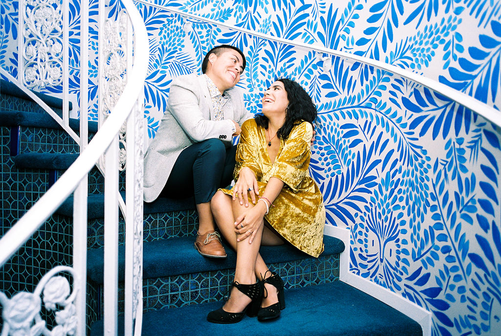 Bilingual, feminist sister officiants looking at each other, smiling, and sitting on a winding staircase with a beautiful blue floral background