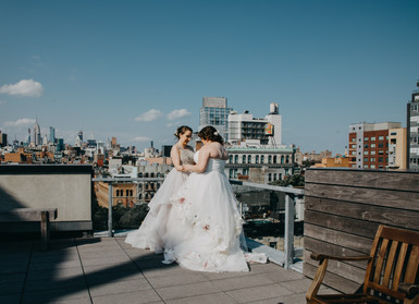 Two caucasian brides facing each other with their hands on each other's forearms on the rooftop with Downtown Manhattan buildings in the background; picture taken before ceremony officiated by lesbian officiant at Once Upon A Vow.