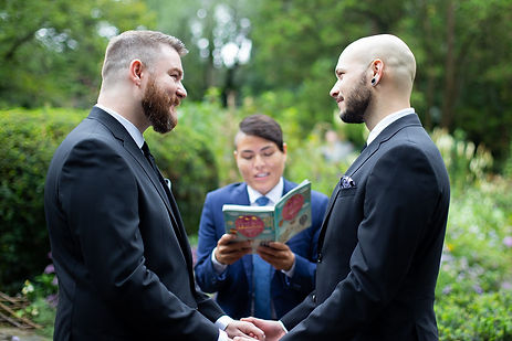 Two smiling grooms getting married in Central Park's Shakespeare Garden by LGBTQ Officiant from Once Upon A Vow