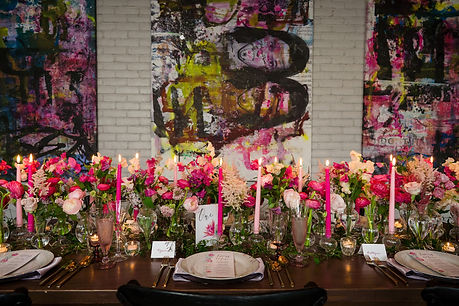 Lush floral and candlelit tablescape with hot and light pink taper candles and colorful pop art background