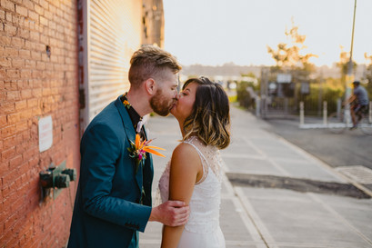 Newly married couple kiss on the Brooklyn sidewalk with the red brick on the left and the golden hour sunset on their right in Greenpoint Brooklyn