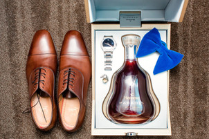 Flat lay photo of the groom's brown leather shoes and a box of Hennessy with royal blue velvet tie, silver watch, and cufflinks positioned on a light brown carpet at the Pelham Bay Golf Course