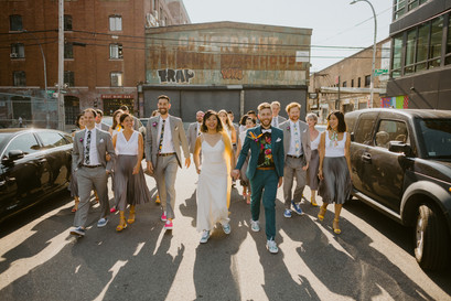 Group photo of couple and their wedding party casually walking in the street, bookended by parked black cars and buildings with some graffiti as their backdrop in Greenpoint, Brooklyn