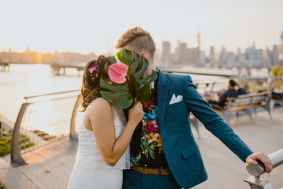 Bride and groom take a moment to stop in Greenpoint's Transmitter Park while they kiss behind her tropical bouquet and the NYC skyline and glowing sunset is behind them