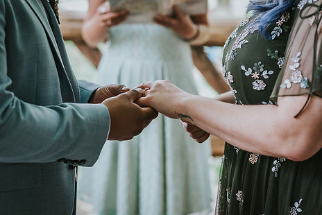 The foreground is focused on hands where groom in light grey suit is placing the wedding band on bride's finger who is wearing an olive green dress with sequins and the background is the spanish-speaking wedding officiant from Once Upon A Vow and her ceremony book.