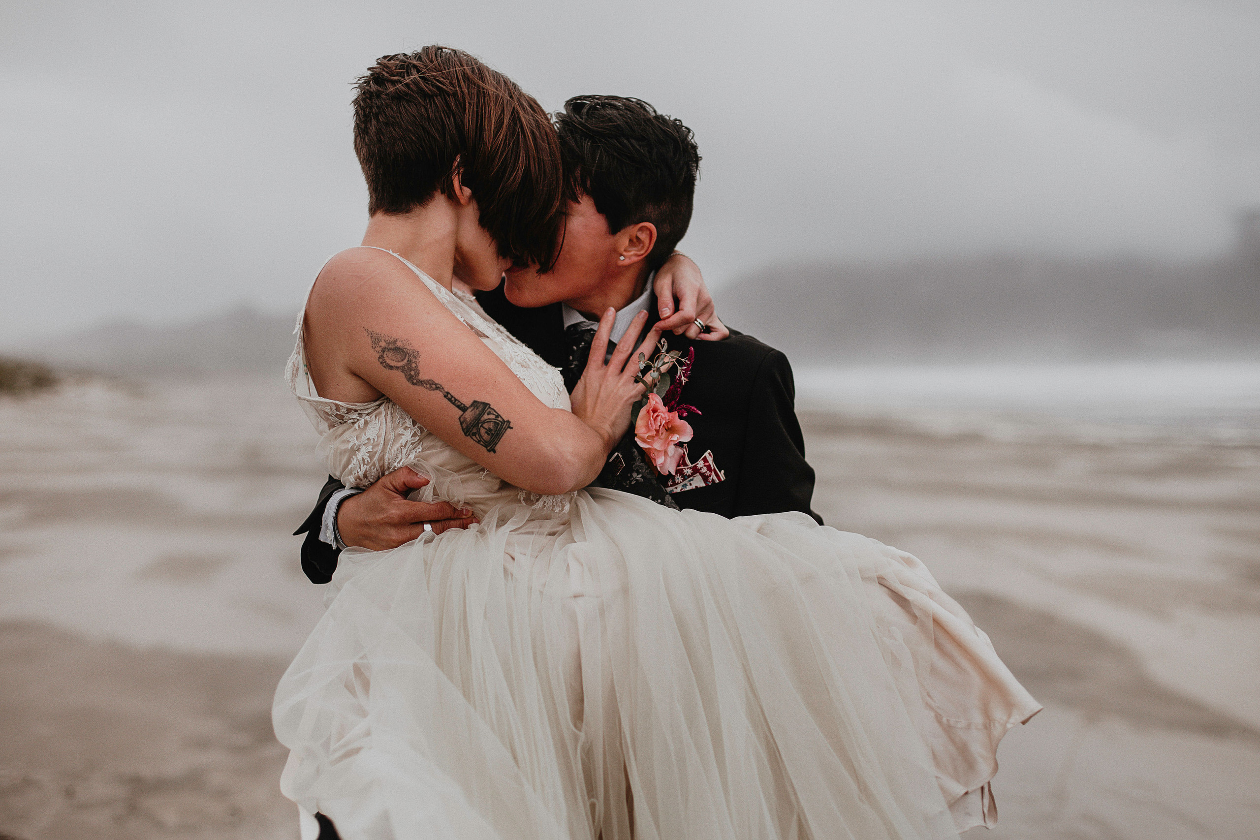 A LGBTQ couple on the beach kissing passionately; the bride in a white vintage dress is being carried by their partner in a black suit, who is known as the queer officiant of Once Upon A Vow