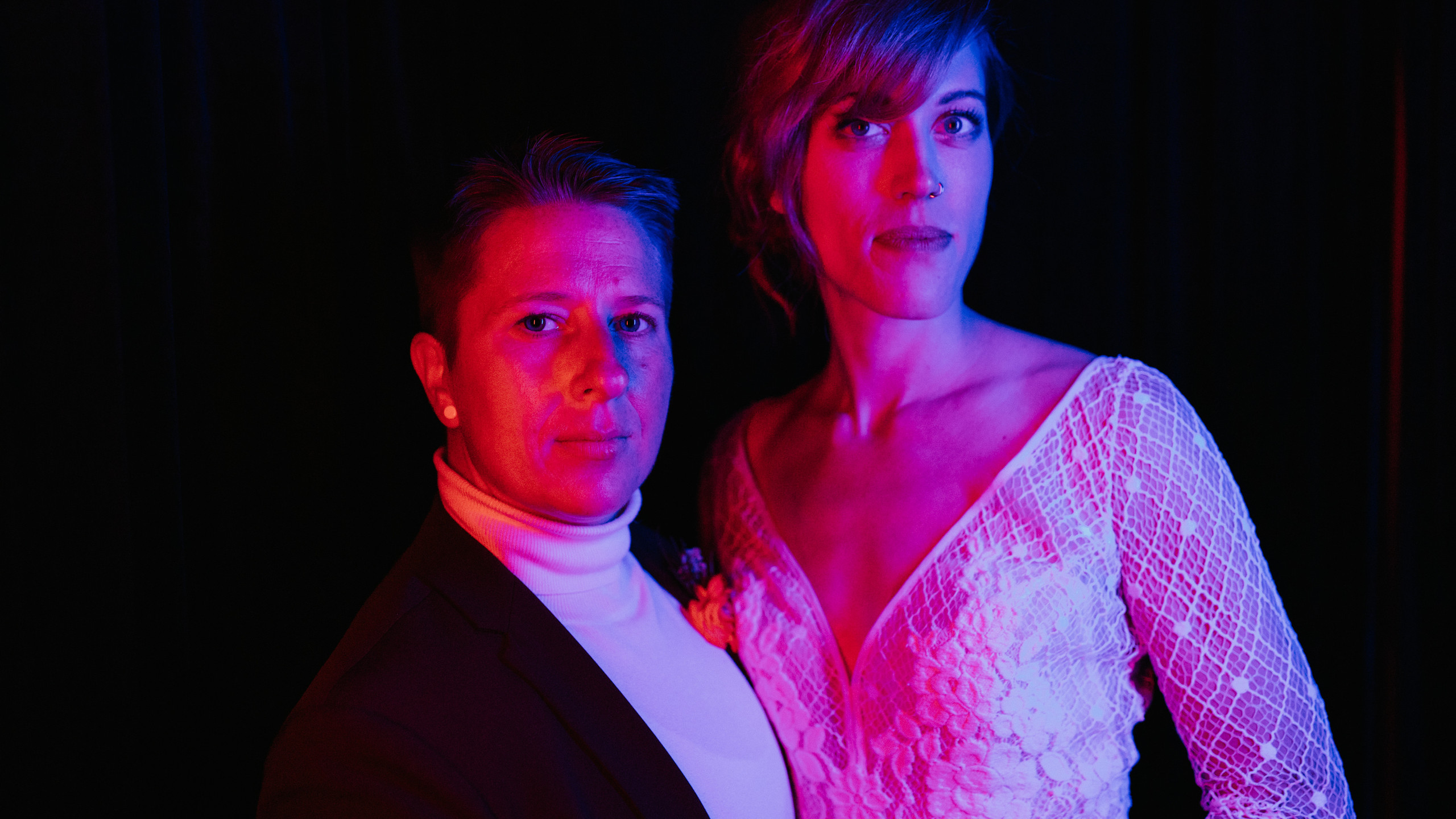 Neon color portrait of LGBTQ couple, one in maroon suit and the other in bridal sequin v-neck dress looking into the camera