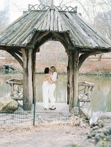 Two brides kissing and embracing at Wagner's Cove under the arch of the little gazebo; post ceremony officiated by lesbian officiant at Once Upon A Vow.