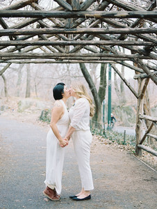 Asian-Canadian and Anglo-American brides holding hands and kissing under a wooden canopy near the 72nd street entrance of Central Park; they're wearing white outfits, one in a halter-top jumpsuit and the other in nice pants and a sweater blouse; each wearing a corsage; picture taken post elopement ceremony officiated by queer officiant at Once Upon A Vow.