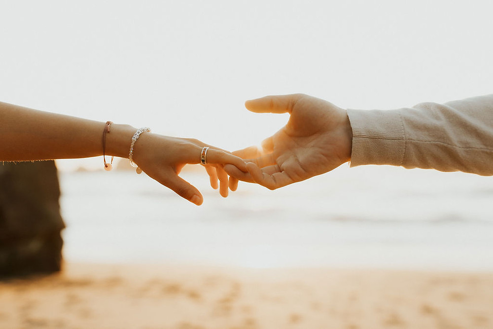 Two hands reaching for each other during golden hour on a beach, one arm is wearing a ring and two bracelets and the other arm is wearing a sweater