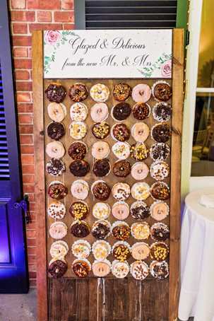 Delicious donut wall with ten rows of varying flavors of donuts hanging on a wooden frame with a sign that says 'glazed and delicious from the new Mr. and Mrs.' laying on exposed brick of the Pelham Bay Golf Course wall.