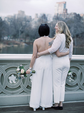 lgTwo brides looking toward the lake from Bow Bridge; the shot is of their backs which shows them with one arm around each other; the Asian-Canadian bride has a right shoulder tattoo of some kind of animal and is holding her bouquet to her side.